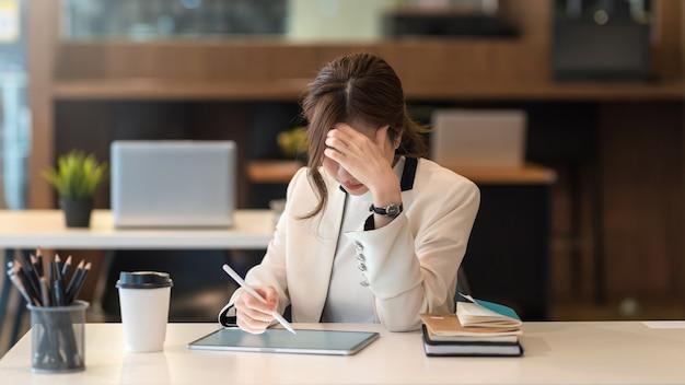 Azjatycka bizneswoman jest zmęczona, znudzona tą samą powtarzalną pracą przy użyciu tabletu w biurze.