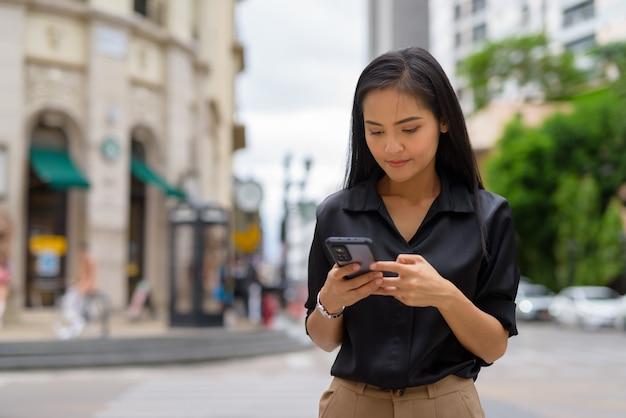 Azjatycka bizneswoman na zewnątrz na ulicy miasta za pomocą telefonu komórkowego podczas wysyłania wiadomości tekstowych