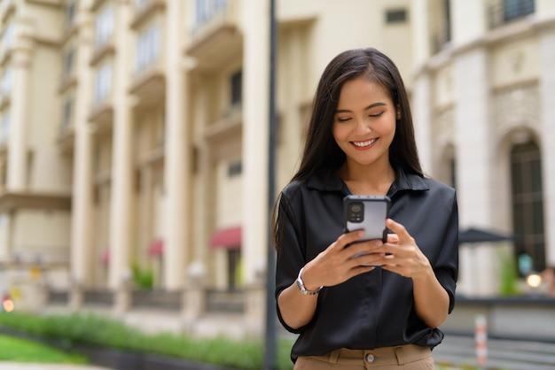 Azjatycka bizneswoman na zewnątrz na ulicy miasta za pomocą telefonu komórkowego, uśmiechając się i wysyłając sms-y