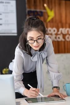 Azjatycka bizneswoman pochyla się przy biurku do pracy w biurze.