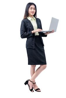 Azjatycka bizneswoman pozycja podczas gdy używać laptop