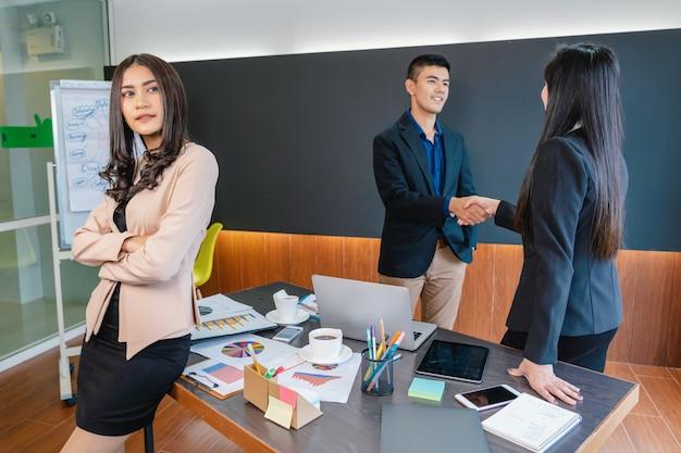 Azjatycka bizneswoman pozycja z lekceważeniem kolega z pracy który stoi i trząść rękę