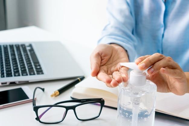 Azjatycka bizneswoman pracuje w miejscu pracy i stosuje żel do dezynfekcji rąk