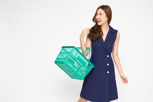 Azjatycka bizneswoman śmiejąca się i trzymająca koszyk na zakupy na białym tle