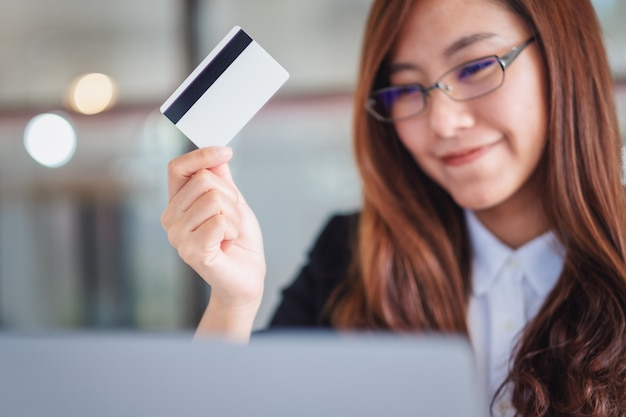 Azjatycka bizneswoman trzymająca karty kredytowe podczas korzystania z laptopa w biurze