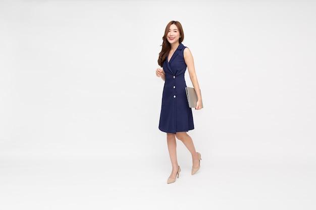 Azjatycka bizneswoman trzymająca laptopa podczas chodzenia na białym tle