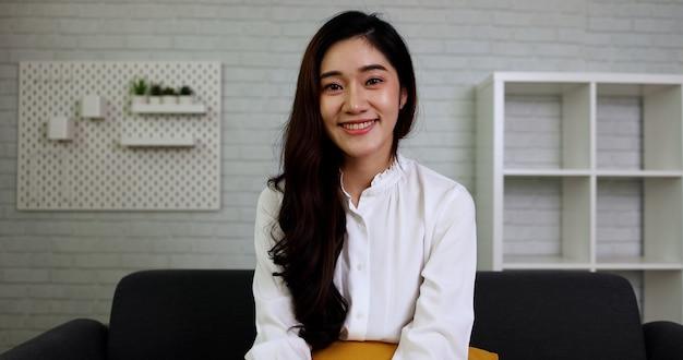 Azjatycka bizneswoman uśmiechnięta i patrząca na kamerę w salonie w domu uczucie szczęśliwej koncepcji