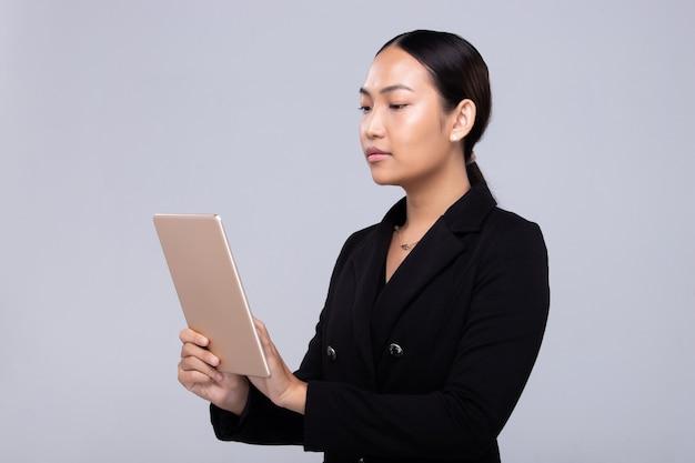 Azjatycka bizneswoman w formalnym garniturze nosić cyfrowy tablet