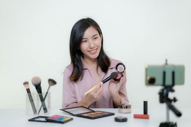 Azjatycka Blogerka Kosmetyczna Kręci Film, Na Którym Nosi Pomarańczową Szminkę W Studiu. Premium Zdjęcia