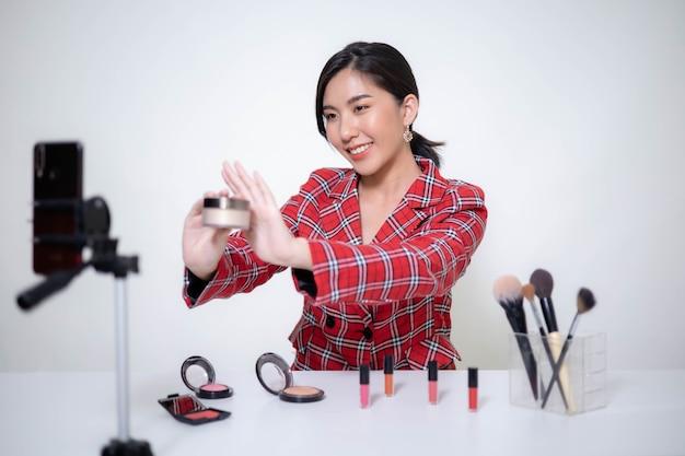 Azjatycka blogerka kosmetyczna robi makijaż, recenzuje kosmetyki na blogu wideo