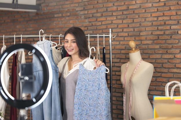 Azjatycka blogerka recenzuje produkt i rozmawiającą kamerę, nagrywając wideo na żywo w sieci społecznościowej w domu, sprzedając ubrania online w mediach społecznościowych