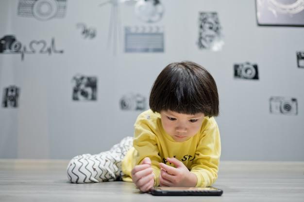 Azjatycka chinka gra w smartfona na podłodze, ogląda smartfon, dziecko używa telefonu i gra, dziecko korzysta z telefonu komórkowego, uzależnia się od gry i kreskówki