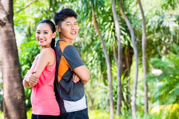 Azjatycka chińska para kończy działającego szkolenie w parku