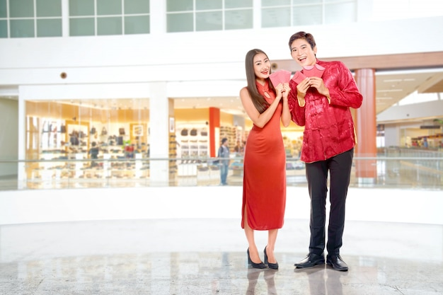 Azjatycka chińska para w cheongsam sukni trzyma czerwone koperty