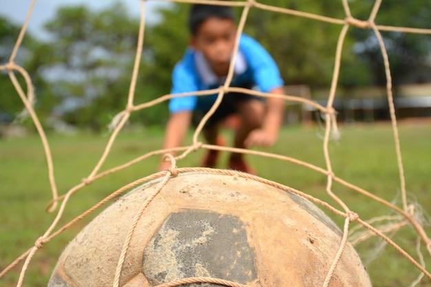 Azjatycka chłopiec bawić się futbol na gazonie