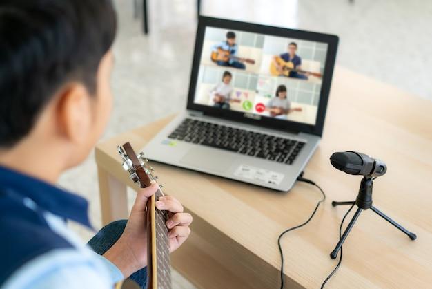 Azjatycka chłopiec bawić się gitarę akustyczną online z przyjaciółmi
