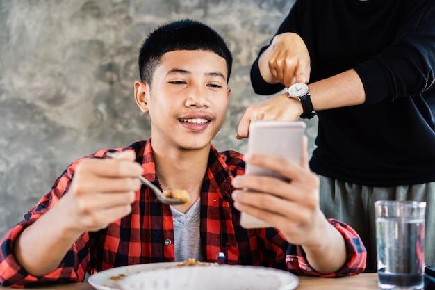 Azjatycka chłopiec bawić się grę podczas gdy jedzący obiad