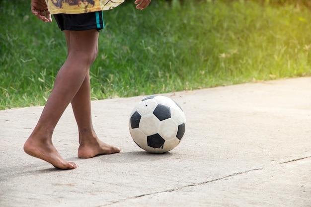 Azjatycka chłopiec bawić się starego futbol na ulicie, dzieciaki bawić się piłkę nożną dla ćwiczenia w wieczór