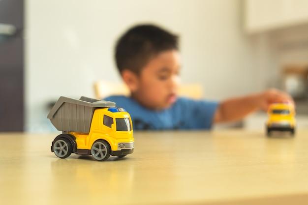 Azjatycka chłopiec bawić się z zabawkarskimi samochodami w domu