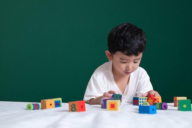 Azjatycka chłopiec bawić się zabawkę lub kwadratowego bloku łamigłówkę na zielonym chalkboard tle