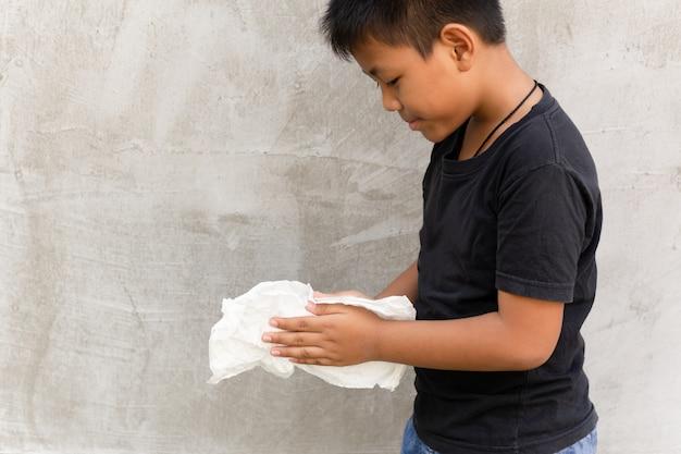 Azjatycka chłopiec czyści jego ręki z mokrą tkanką.