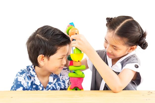 Azjatycka chłopiec i dziewczyna szczęśliwie bawić się kolorową drewnianego bloku zabawkę