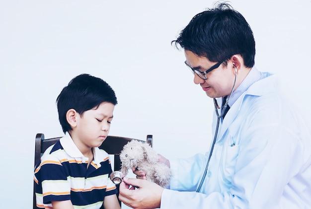 Azjatycka chłopiec i lekarka podczas egzamininować używać stetoskop nad białym tłem
