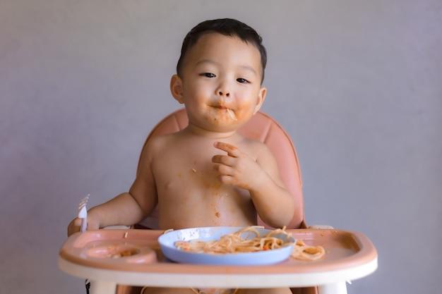 Azjatycka chłopiec je na wysokim dziecka krześle.