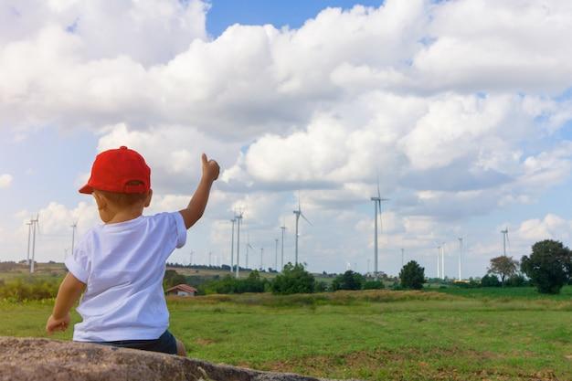 Azjatycka chłopiec jest ubranym czerwonego kapelusz siedzi i patrzeje wiele turbina wiatrowa.