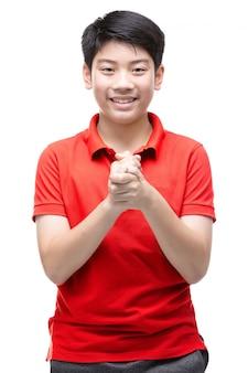 Azjatycka chłopiec jest ubranym czerwonego koszulowego modlenie