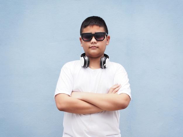 Azjatycka chłopiec jest ubranym hełmofon nad błękit ściany tłem z białą koszula.