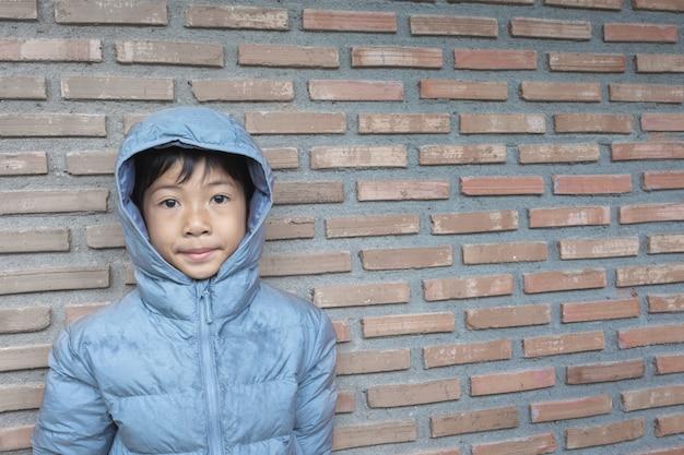 Azjatycka chłopiec jest ubranym kapiszon na ściana z cegieł tle