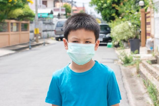 Azjatycka chłopiec jest ubranym maskową pozycję na ulicie w bangkok, tajlandia.