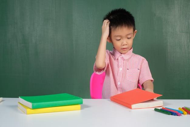 Azjatycka chłopiec myśleć o pytaniu w kredowej deski pokoju