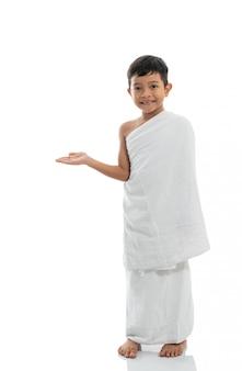 Azjatycka chłopiec przedstawia copyspace z ihram.