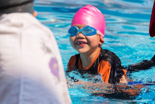 Azjatycka chłopiec przy pływackiego basenu dnia czasem
