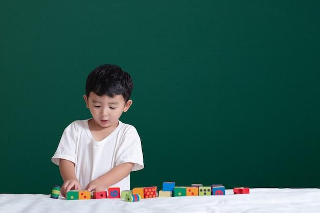 Azjatycka chłopiec sztuki zabawka lub kwadratowego bloku łamigłówka na zielonym chalkboard
