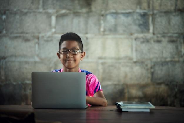 Azjatycka chłopiec używa laptop na stole, wraca czerpać
