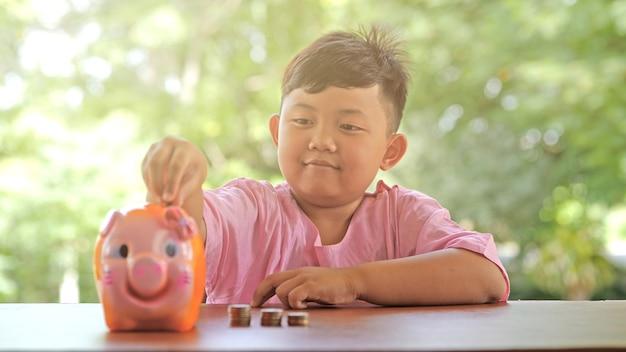 Azjatycka chłopiec z szczęśliwą uśmiech zabawy kładzenia monetami w prosiątko banku