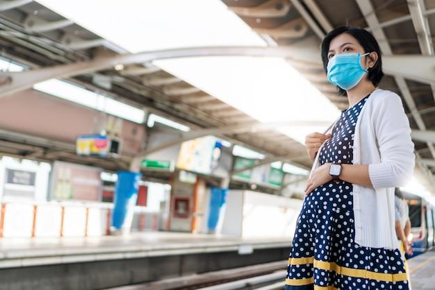 Azjatycka ciążowa kobieta jest ubranym twarzy maskę czeka niebo pociąg w nowym normalnym