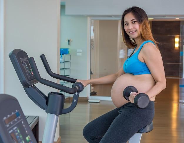 Azjatycka ciężarna kobieta ćwiczy w sportowym pokoju, ridindg rower i podnośnego dumbbell