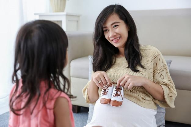 Azjatycka ciężarna macierzysta mienia dziecka buty