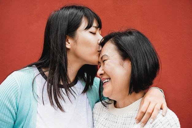 Azjatycka córka całuje mamę w dzień matki