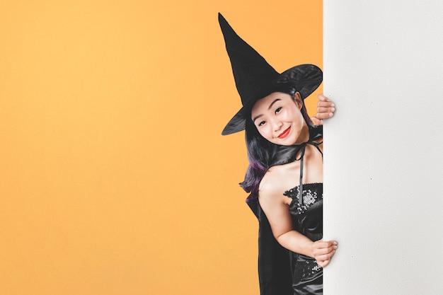 Azjatycka czarownica kobieta w kapeluszu stojąca z pustą deską na kolorowym tle. pusta płyta do miejsca na kopię