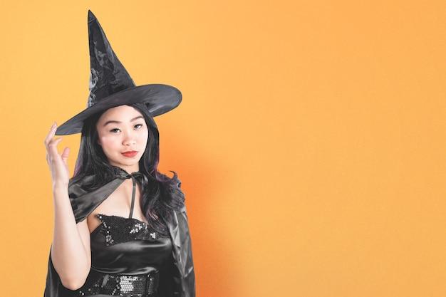 Azjatycka czarownica kobieta w kapeluszu stojący z kolorowym tłem