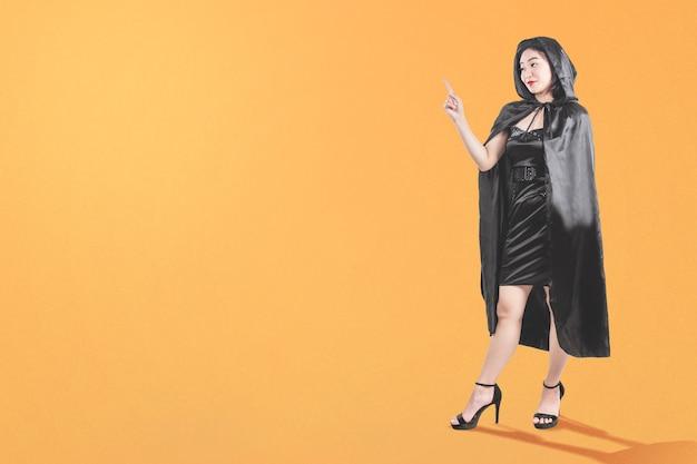 Azjatycka czarownica kobieta z płaszczem, wskazując coś na kolorowym tle
