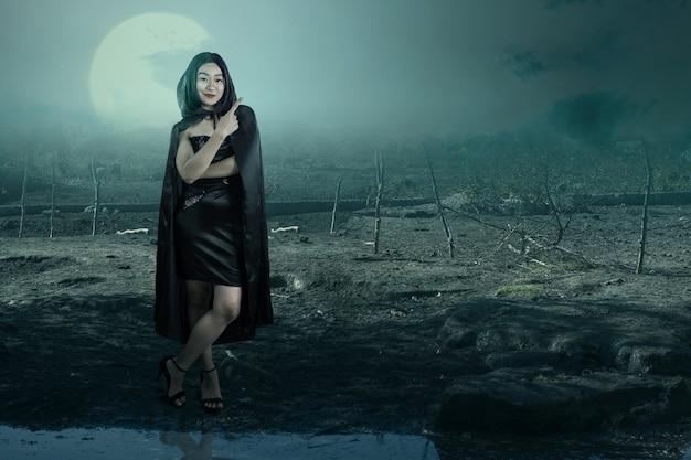 Azjatycka czarownica kobieta z płaszczem, wskazując coś z nawiedzonym polem