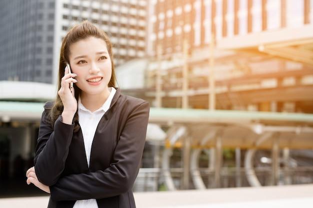 Azjatycka dama korzysta z telefonu smartphone w sieci społecznościowej.