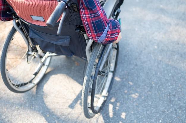 Azjatycka dama na wózku inwalidzkim w parku