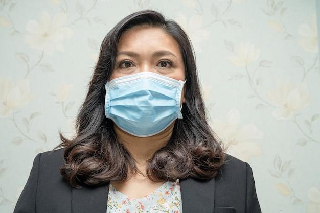 Azjatycka dama nosząca maskę nową normalną w biurze w celu ochrony przed infekcją covid-19 coronavirus.